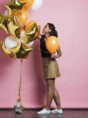 Side view of cheerful young African-American female in trendy leather skirt and sneakers taking bright orange balloon from colorful bunch hanging nearby and smiling standing over pink studio background