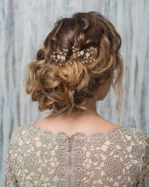 Woman with beautiful hairstyle decorated by fancy shiny hair accessory, rear view