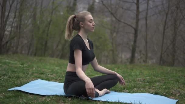 Žena cvičit jógu sedí v lotosu pózovat na trávě venku