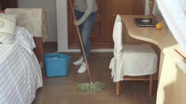 Žena tření podlahy v ložnici