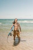 young man with surfboard standing in ocean on summer day