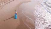 a légi felvétel a nő fehér fürdőruha húzza szörfdeszka, homokos strandon, Ashdod, Izrael