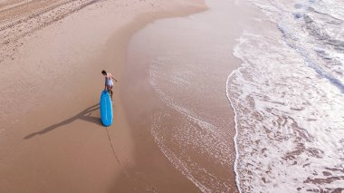 aerial view of woman in white swimsuit pulling surfboard on sandy beach, Ashdod, Israel