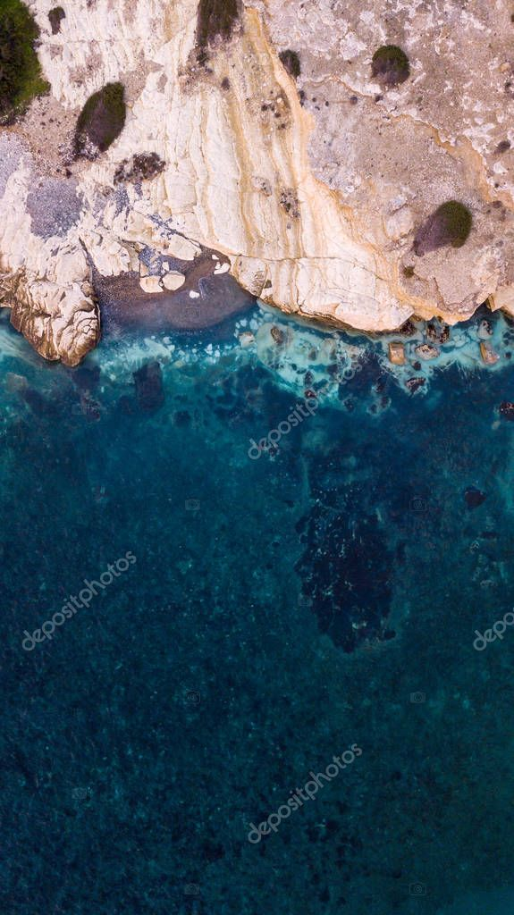 aerial view of beautiful sandstone rocks on seashore with blue water, Cyprus