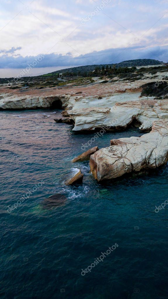 aerial view of sandstone rocks on seashore with blue water under cloudy sky, Cyprus