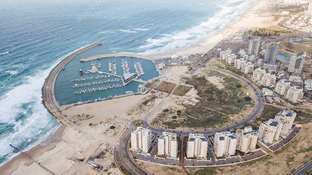 aerial view of circle arranged houses and harbor on sea coast, Ashdod, Israel