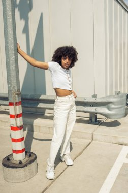 beautiful stylish african american girl leaning at pole and looking at camera on street