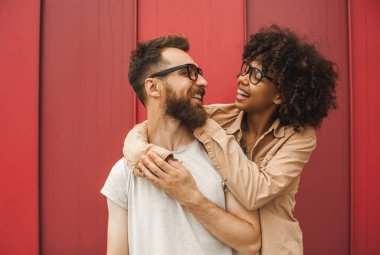 happy young interracial couple in eyeglasses hugging and smiling each other