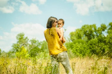 mother holding son in field at sunny day