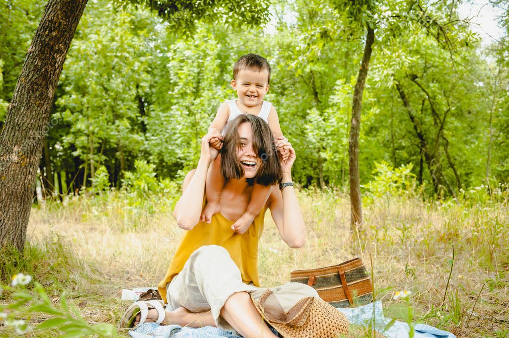 happy mother holding son on shoulders at picnic