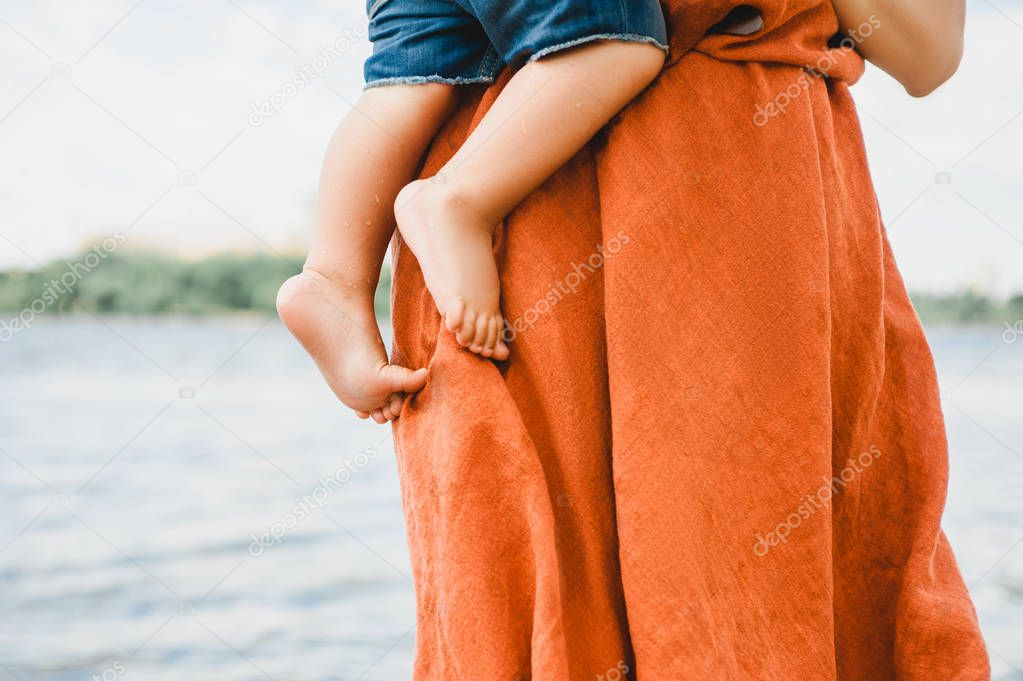 cropped image of mother in dress holding son near river
