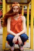 elegant stylish girl with red hair posing in orange headband