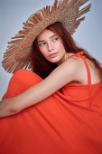 beautiful redhead woman posing in red dress and straw hat, isolated on grey