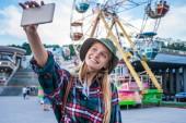 Fotografia bella ragazza bionda sorridente tenendo selfie con smartphone nel parco di divertimenti