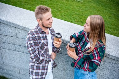 high angle view of young couple holding paper cups and smiling each other