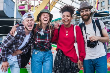 happy young multiethnic friends standing together and laughing in amusement park