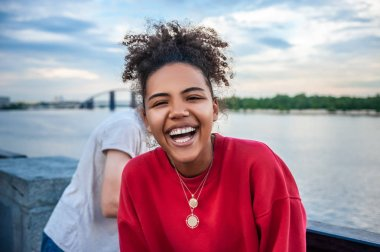 beautiful happy young african american woman laughing at riverbank