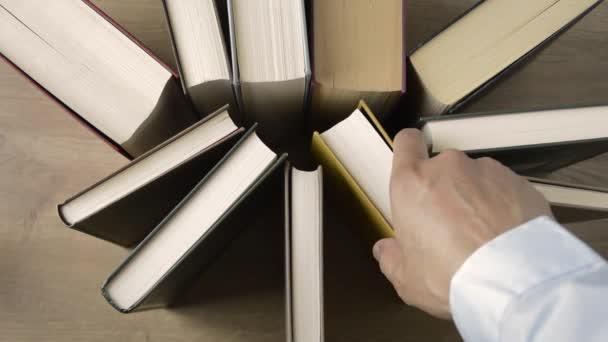 Ruka osoby zvedající knihu z knihovny, která je na dřevěném stole