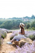 side view of pregnant woman sitting on hay bale in violet lavender field and touching belly