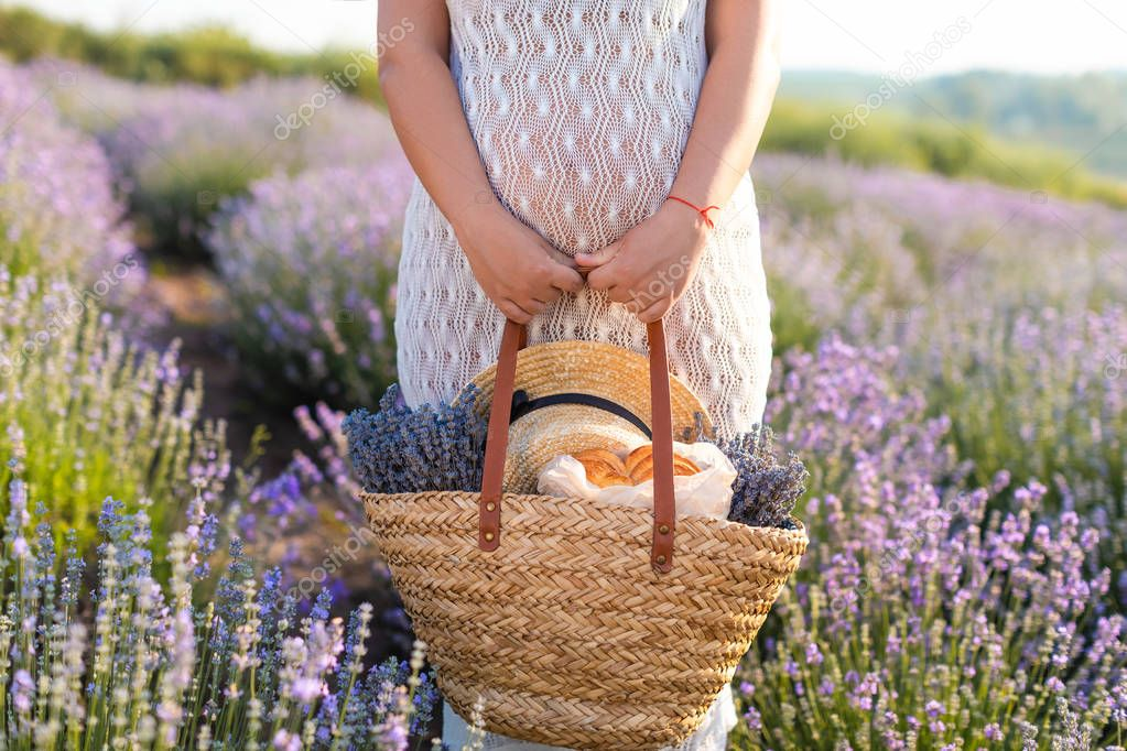 cropped image of pregnant woman in white dress holding picnic basket at violet lavender field