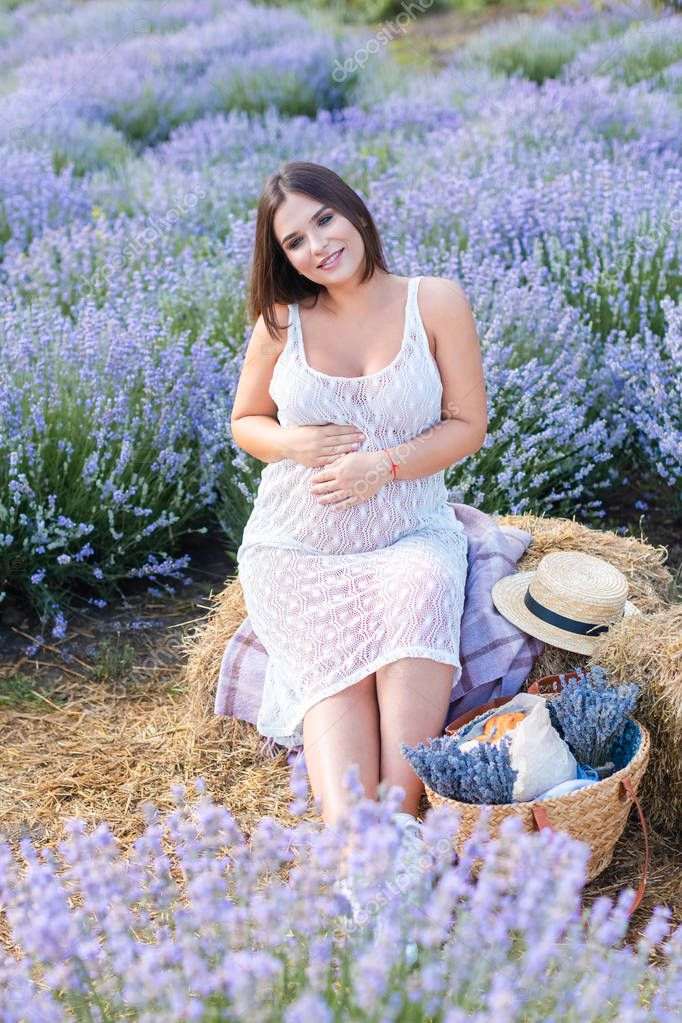 smiling pregnant woman sitting on hay bale in violet lavender field and touching belly