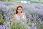 Beautiful woman in straw hat sitting in violet lavender field