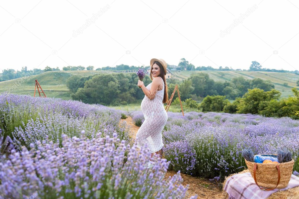beautiful pregnant woman in white dress at violet lavender field with picnic basket on hay bale
