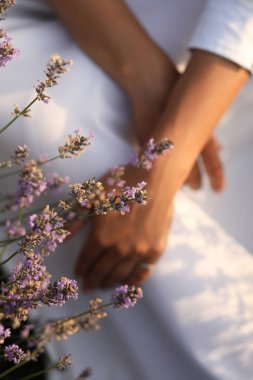 cropped image of woman in white dress with violet lavender flowers