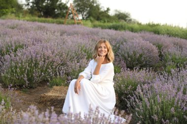 smiling attractive woman in white dress sitting in violet lavender field