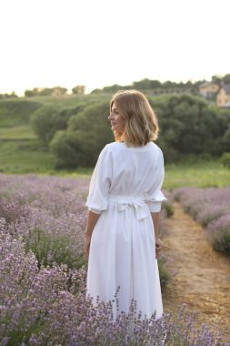 back view of attractive woman in white dress standing in violet lavender field
