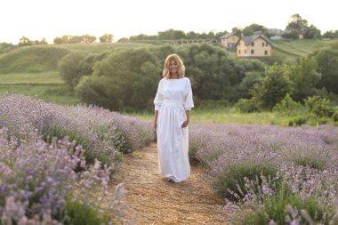 attractive woman in white dress standing on path in violet lavender field