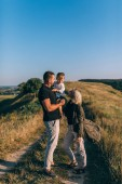 Photo smiling young parents looking at adorable little son while standing on rural trail