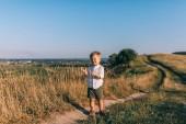 po celé délce pohled milý chlapeček, stojící na venkovské cestě a při pohledu na fotoaparát