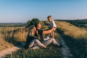 Photo happy parents playing with little son while sitting together on rural trail
