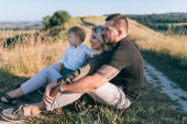 Photo happy parents with adorable little son sitting and looking away in rural landscape