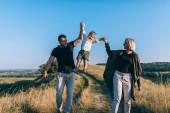 Fotografie šťastní rodiče s rozkošný malý syn, drželi se za ruce a baví na venkově stezka