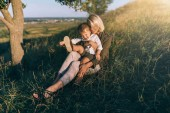 Photo smiling young mother and cute little son sitting together on green grass at sunset