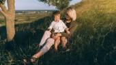 šťastná Maminka a roztomilý malý syn sedí společně na zelené trávě při západu slunce