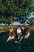 Fotografie glückliche Familie mit einem Kind zusammen ruhen auf dem grünen Rasen