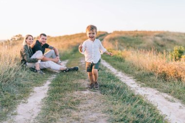 happy parents looking at adorable smiling little son running on trail