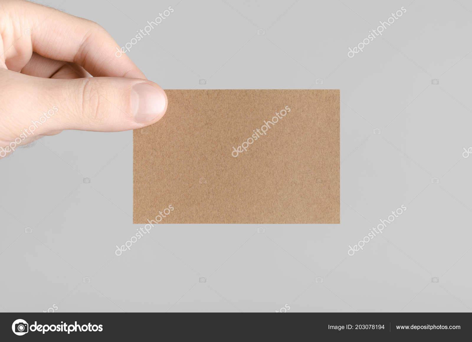 Kraft business card mock 85x55mm male hands holding kraft card kraft business card mock 85x55mm male hands holding kraft card fotografia de stock reheart Images