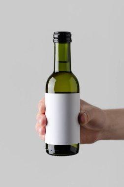 Wine Quarter / Mini Bottle Mock-Up. Blank Label - Male hands holding a wine bottle on a gray background