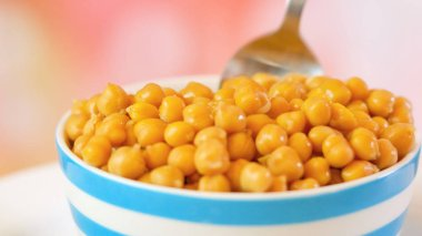 Chickpeas, garbanzo beans, in bowl closeup with spoon.