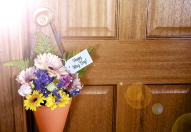 Happy May Day gift of flowers on door with lens flare.