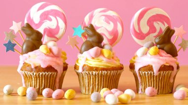 Easter theme candy land drip cupcakes in party table setting.