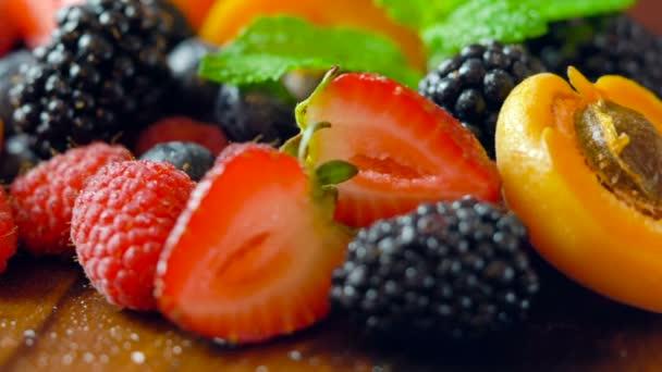 Macro closeup of rotating mixed summer fruit on wooden table.