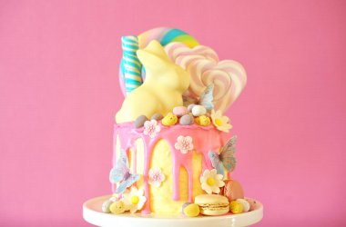 Easter candy land drip cake decorated with lollipops and white bunny.