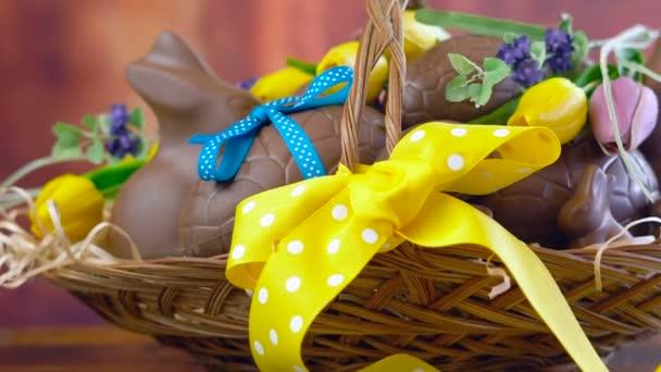 Happy Easter hamper of chocolate eggs in basket, panning macro.