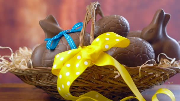 Happy Easter hamper, stacking chocolate eggs and bunny rabbits in large basket.