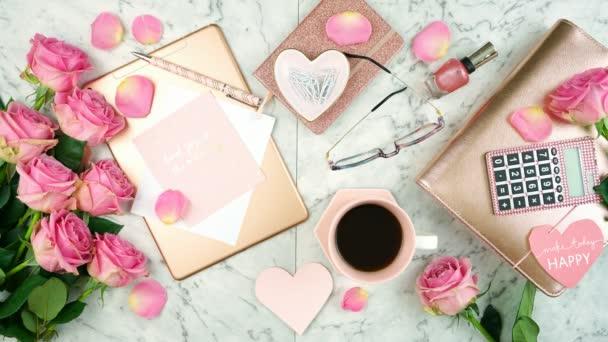 Ultra ženský stůl pracovní prostor s růžovým zlatým příslušenstvím flatlay stop motion.